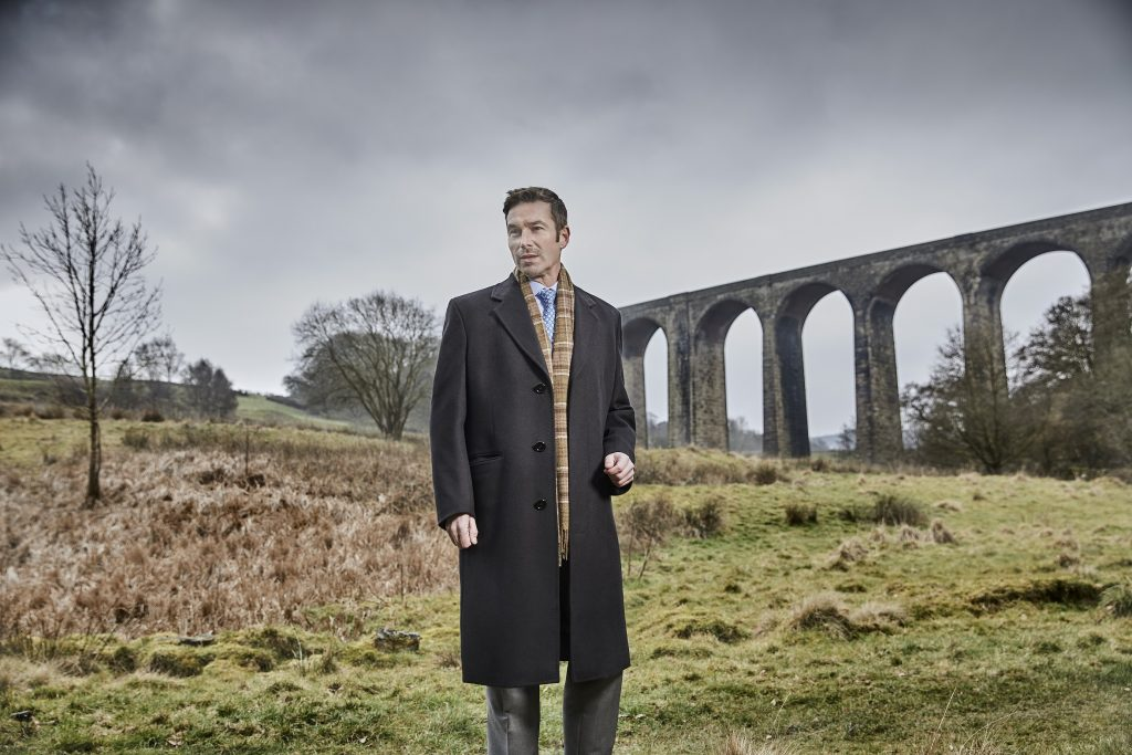 A male model stands in from of a Yorkshire landscape of grassy hills and a viaduct wearing a smart grey coat made from Standeven's Everest Autumn/ Winter cloths