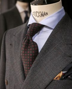 A tailor's dummy wears a suit jacket made from Autumn/ Winter Cloths Heritage Twist in a grey and brown checked design