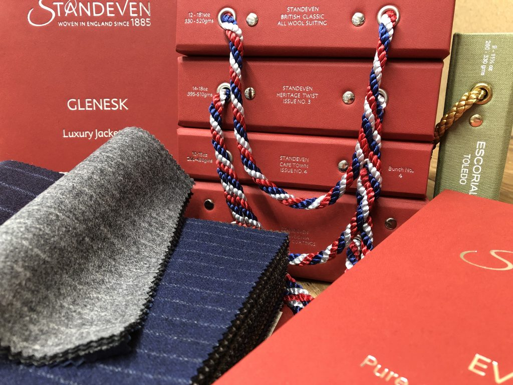 Bunches of Standeven's Autumn/ Winter cloths are displayed in red books with gold embossed labels.